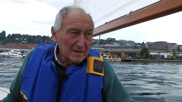 Dick Wagner at helm of sailboat during interview for website.  WATCH VIDEO EXCERPT